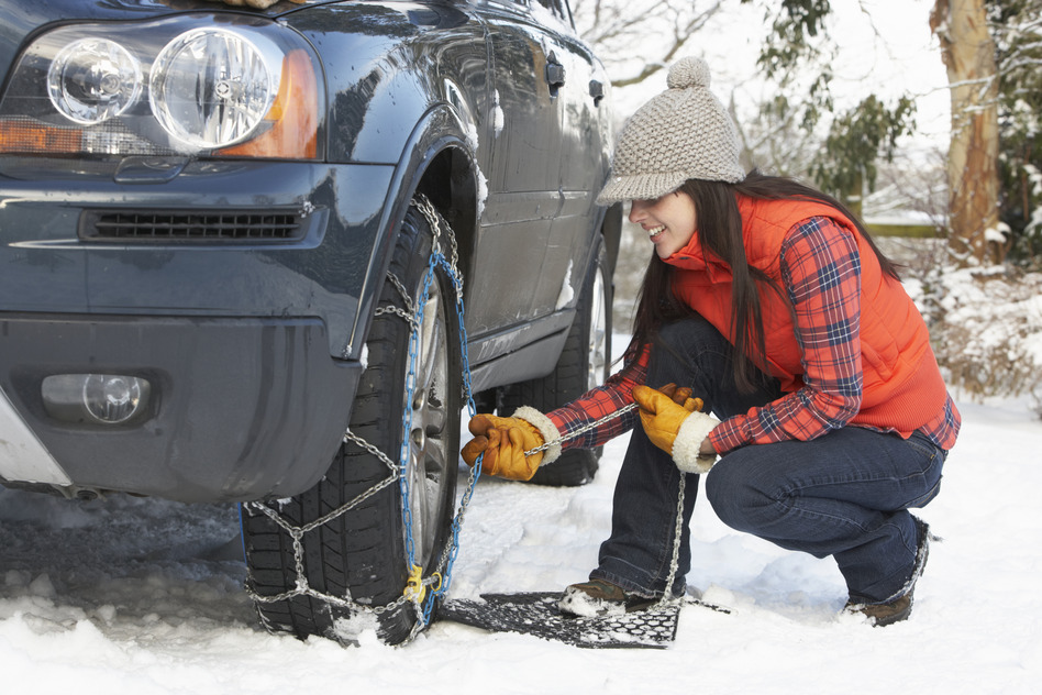 Woman Putting on Snow Chairs on Car Tire