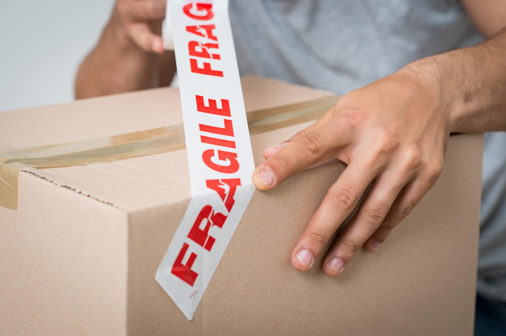 Man Sealing Fragile Item in Moving Box