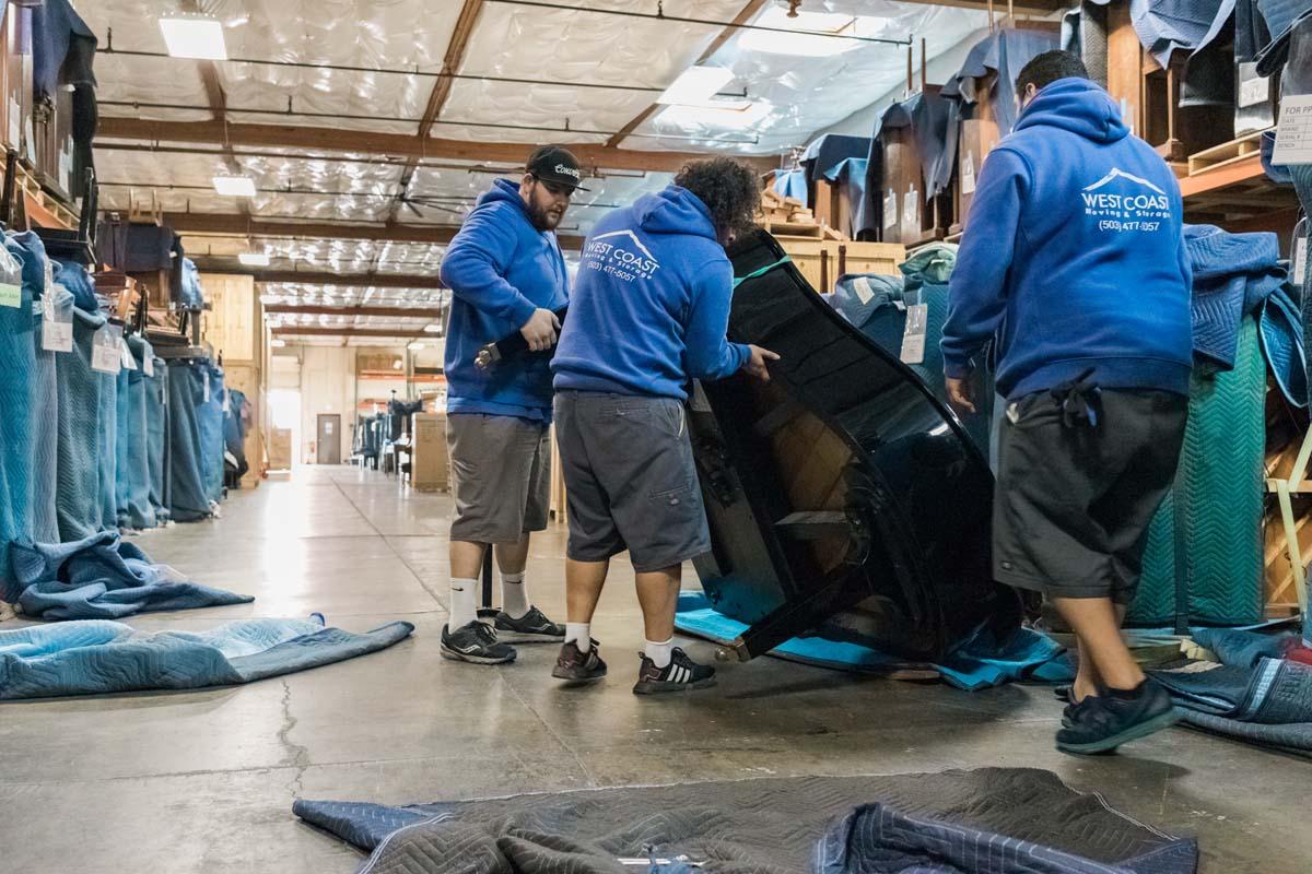 Piano movers carefully wrapping grand piano at storage facility