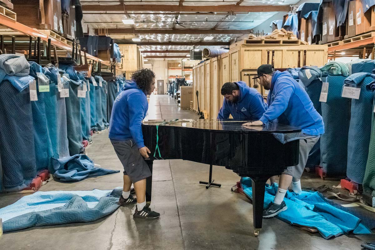 Piano movers adjusting legs on grand piano at Portland storage facility