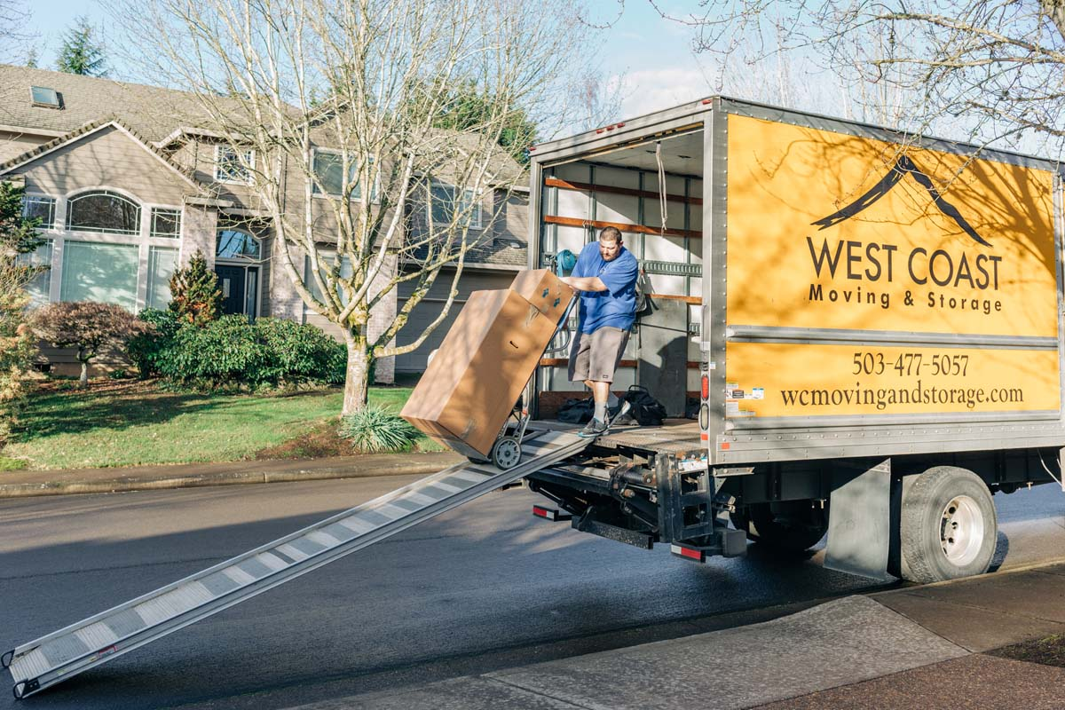 West Coast Moving staff unloading box from truck on dolly