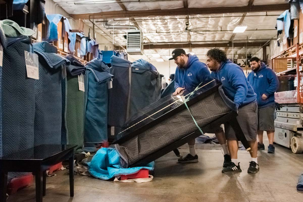 Movers carefully tilting padded piano in climate controlled storage facility
