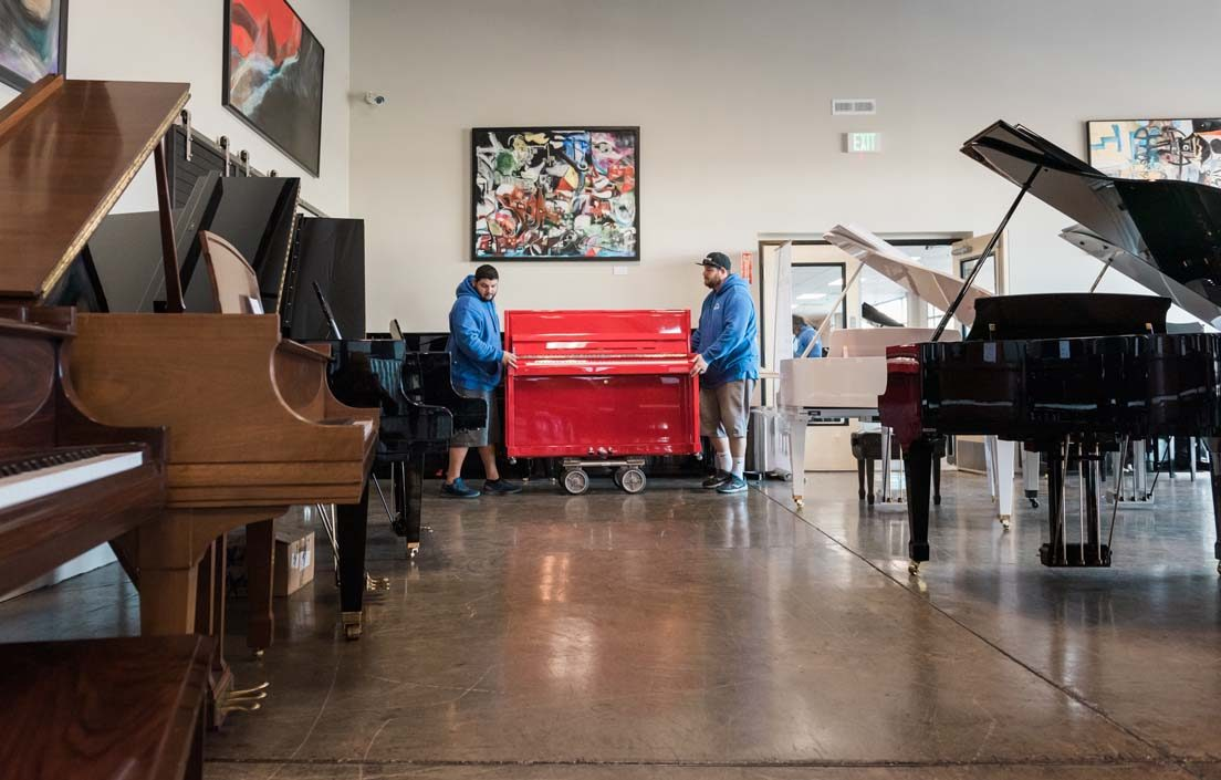 Piano movers transporting red piano to storage facility