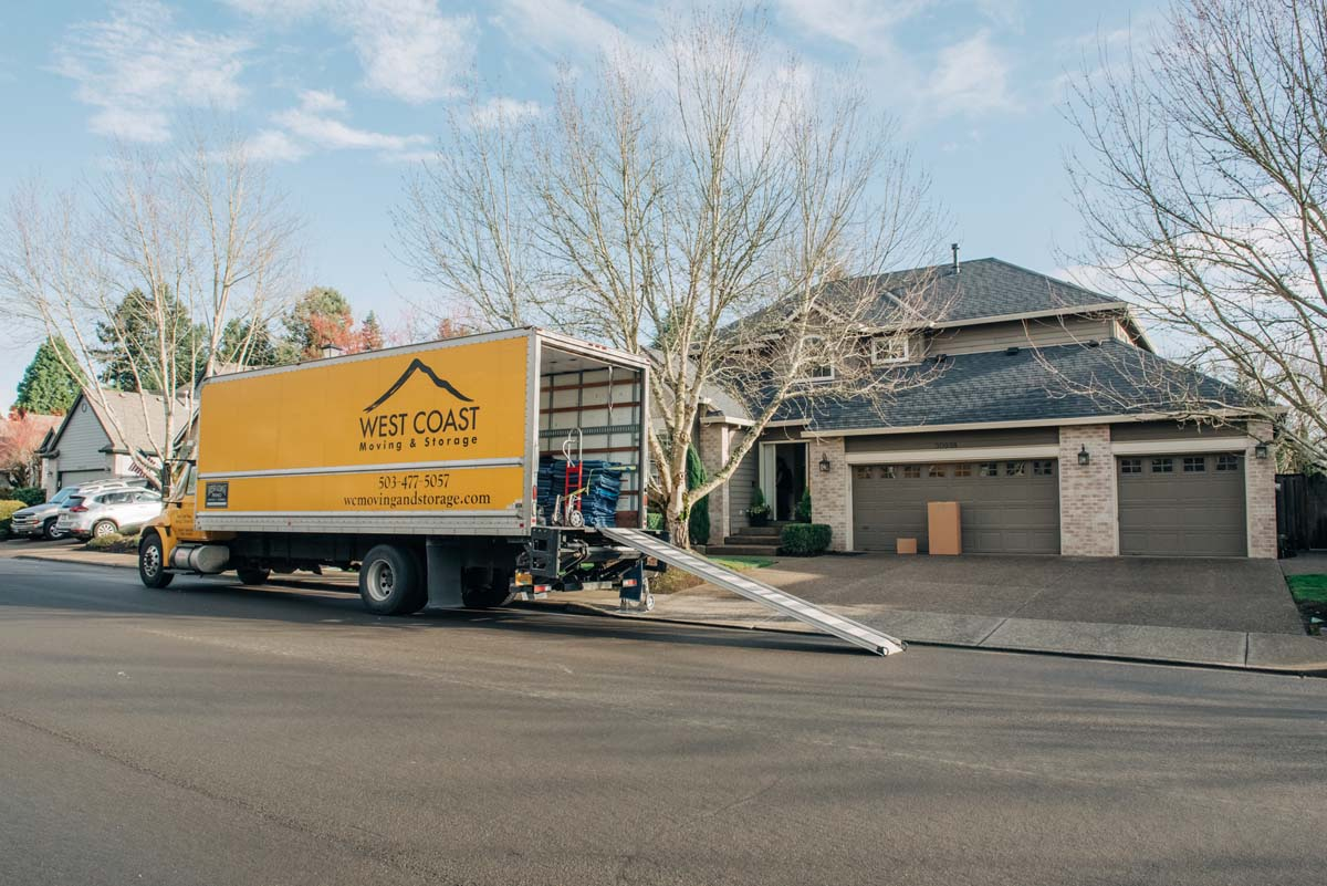 Yellow West Coast Moving & Storage truck outside residential home