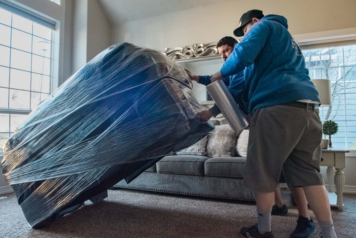 Movers wrapping loveseat for protection during move