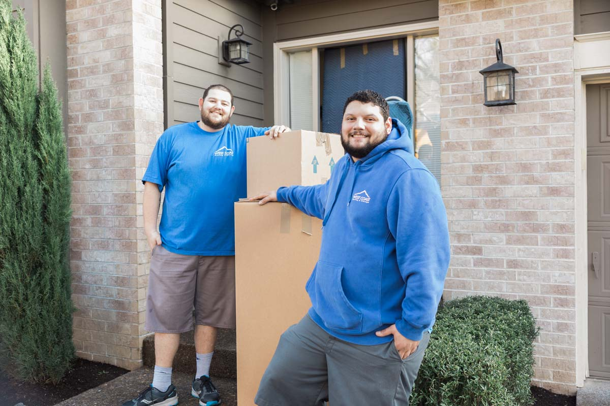 Smiling West Coast moving crew next to boxes