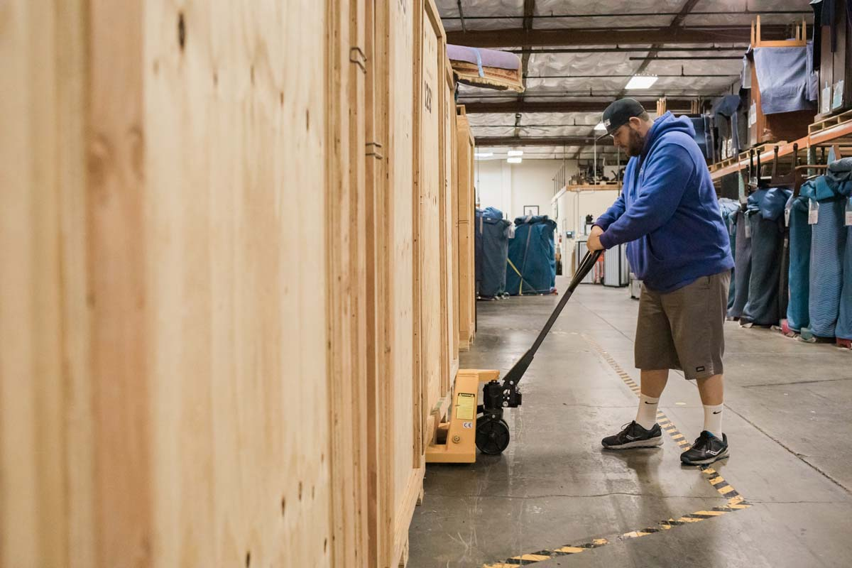 Mover using pallet jack to transport wooden vault in commercial storage facility