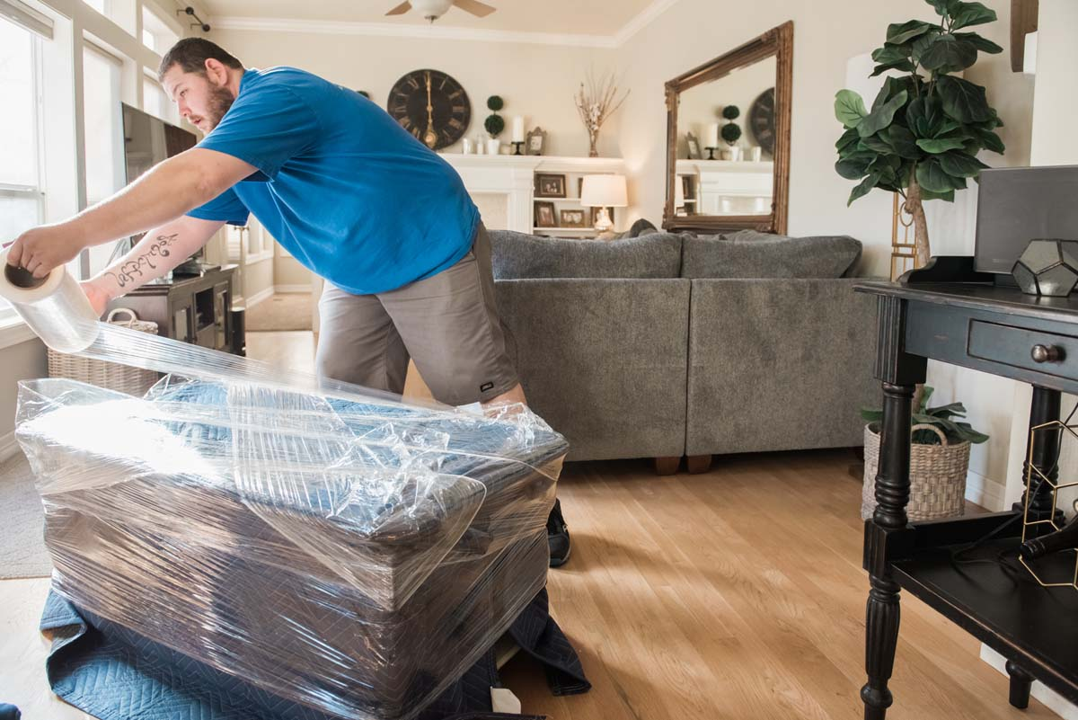 Professional packer wrapping furniture for moving