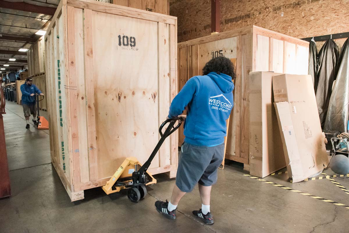 Movers transporting large wooden storage vault box