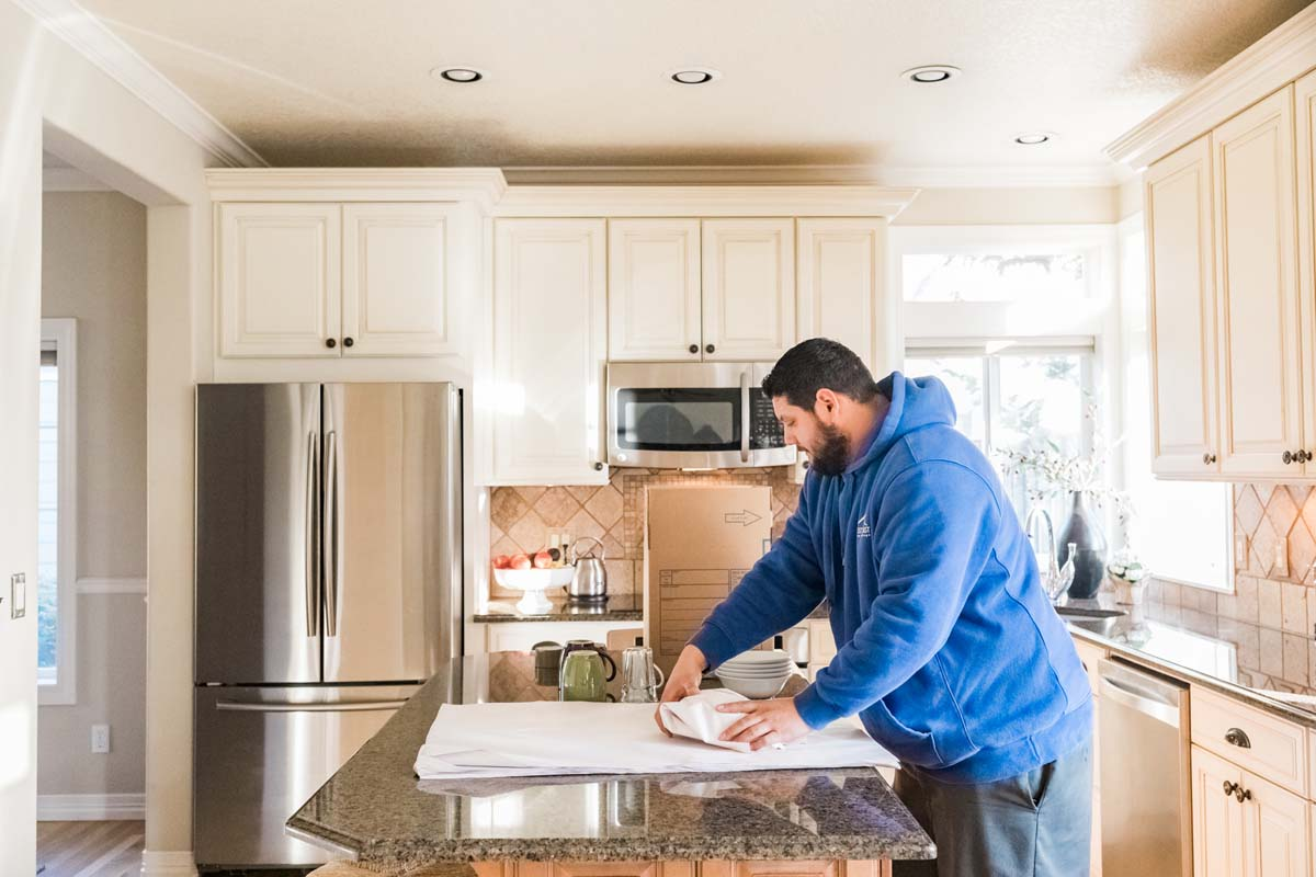 West Coast mover wrapping bowls in residential kitchen