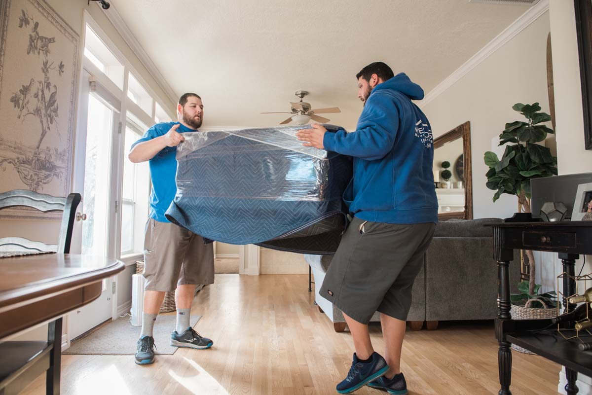 Household movers lifting wrapped and padded furniture