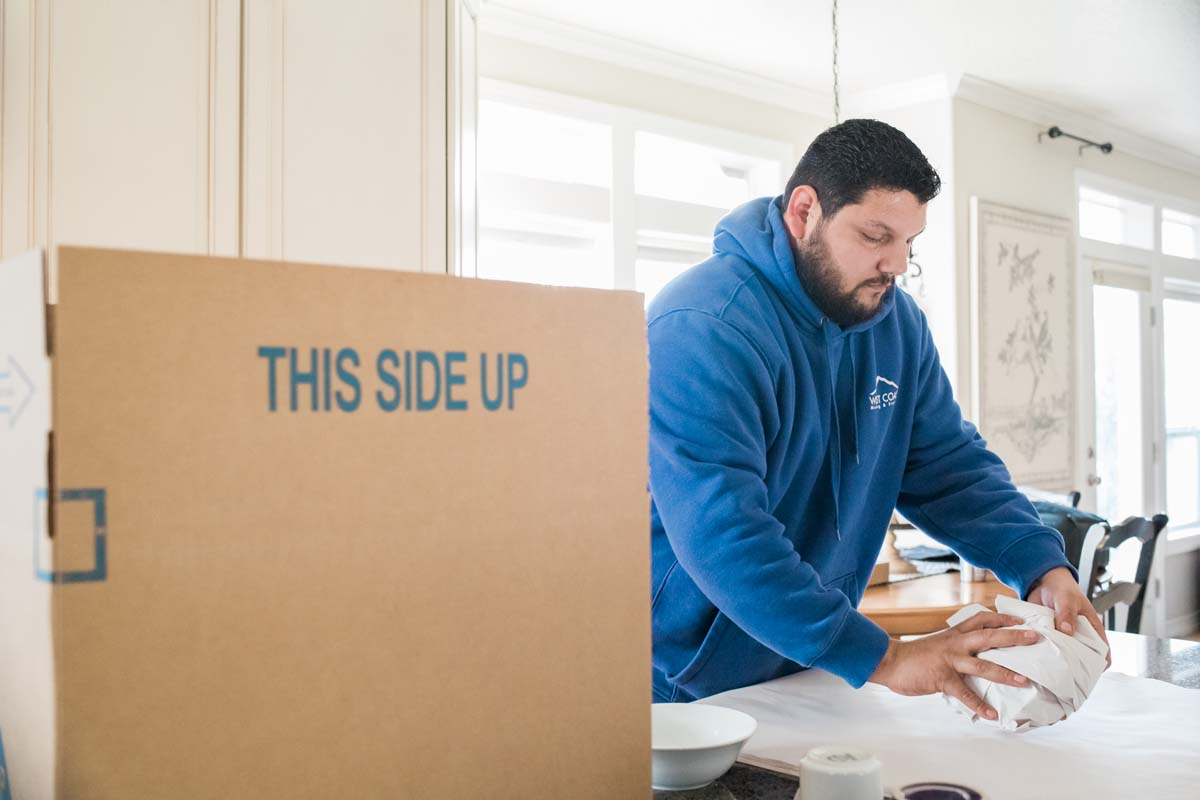 Mover packing fragile dishes in kitchen