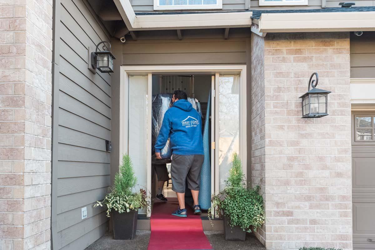 West Coast Moving & Storage team lifting furniture through household doorway
