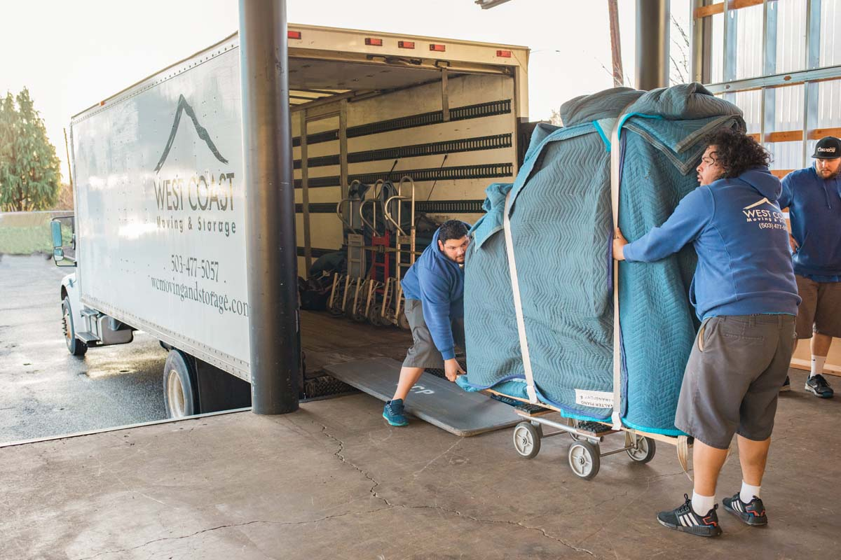 Local movers loading piano onto truck to bring to storage facility
