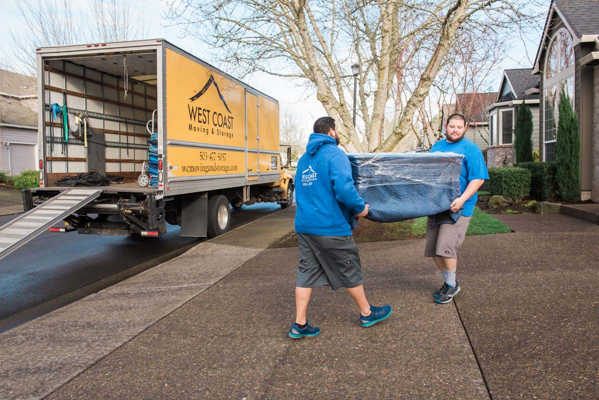 Movers lifting wrapped and padded furniture into house from truck