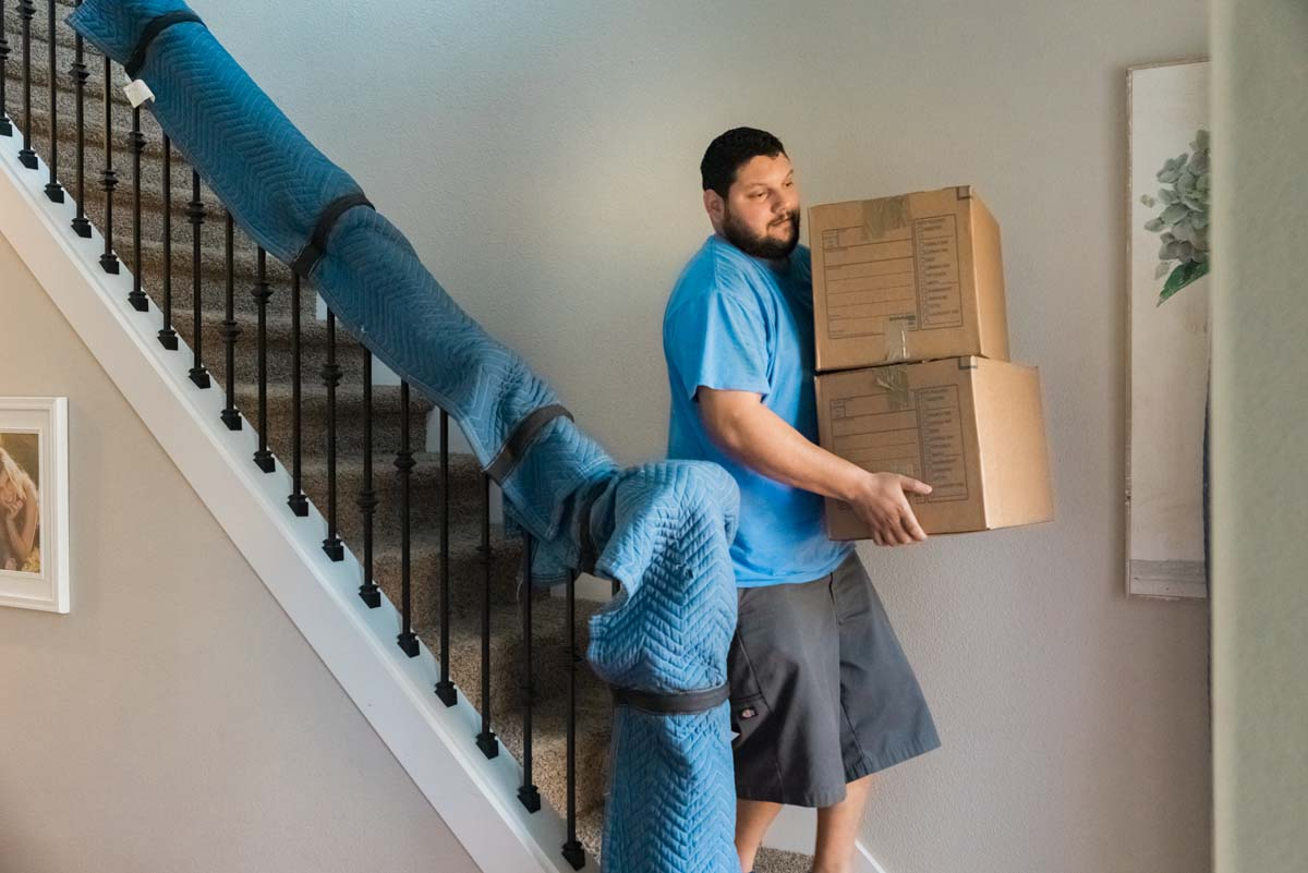 West Coast mover carrying boxes down stairs