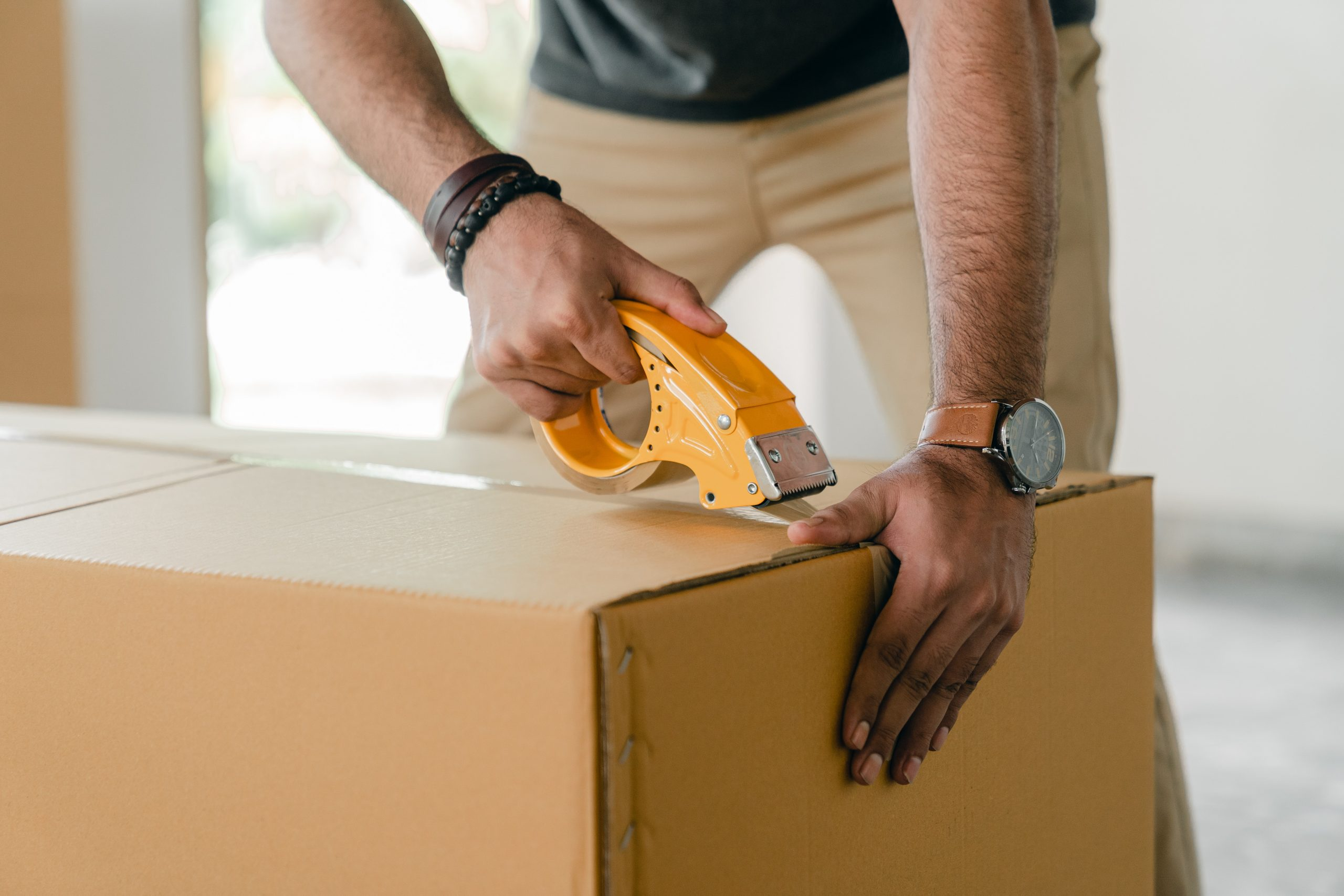 african american man using tape to close a cardboard box for moving